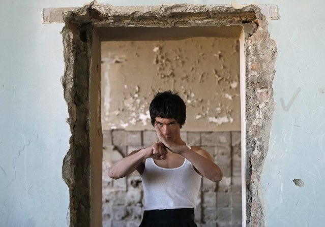 Abbas Alizada, who calls himself the Afghan Bruce Lee, poses during a media event in Kabul December 9, 2014. From the ruins of an iconic bombed-out palace above Kabul, the young Afghan man bearing a striking resemblance to kung fu legend Bruce Lee is high-kicking his way to Internet fame, aiming to show another side to his war-weary nation. (Photo by Mohammad Ismail/Reuters)