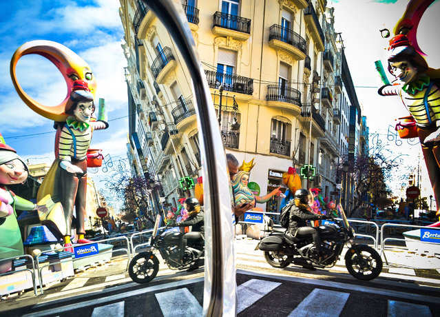 "A ""ninot"" or wooden sculpture is reflected in a street mirror in Valencia, Spain, 13 March 2018, during preparations for the Fallas Festival. Works are being finished for the celebrations of Valencia's traditional Fallas feast that kicks off annually on 15 March and ends on 19 March with a big fire in which puppets and wooden sculptures are set alight, accompanied by fireworks and other forms of pyrotechnics. (Photo by Jose Villalgordo/EPA/EFE)"