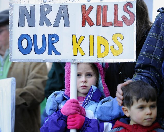 Abigail Garrett of Hampden holds a saign during a rally at the Capitol in Hartford, Conn., Thursday, February 14, 2013. Thousands of people turned out to call on lawmakers to toughen gun laws in light of the December elementary school shooting in Newtown that left 26 students and educators dead. (Photo by Jessica Hill/AP Photo)