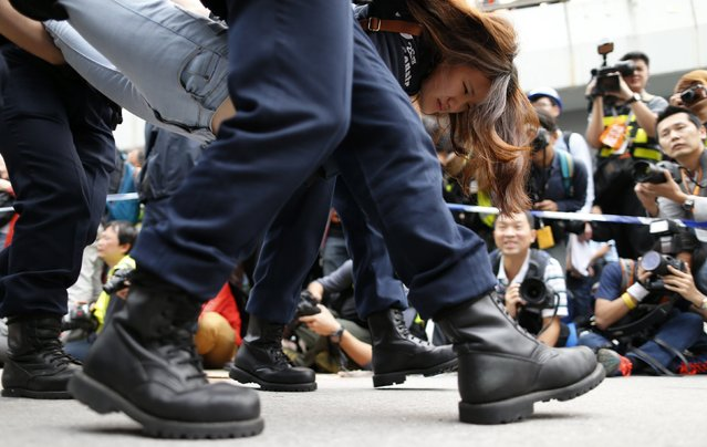A demonstrator is taken away by police from an area previously blocked by pro-democracy supporters, outside the government headquarters in Hong Kong, December 11, 2014. Hong Kong authorities started on Thursday clearing the main pro-democracy protest site that has choked roads into the city's most economically and politically important district for more than two months as part of a campaign to demand free elections. (Photo by Tyrone Siu/Reuters)