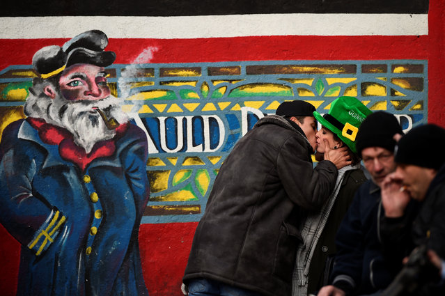 A couple kiss on St. Patrick's Day in Dublin, Ireland on March 17, 2018. (Photo by Clodagh Kilcoyne/Reuters)