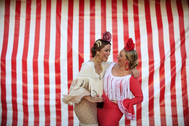 Women wearing typical Sevillana outfits laugh during the traditional Feria de Abril (April fair) in the Andalusian capital of Seville, southern Spain April 18, 2013. The fair will run until April 21. (Photo by Marcelo del Pozo/Reuters)