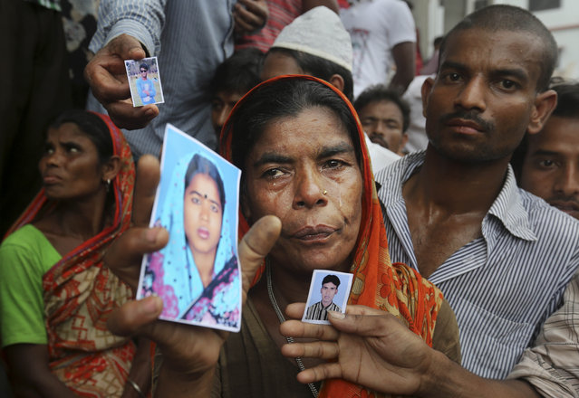 A Bangladeshi weeps as she holds a picture of a missing relative with others at the site of a building that collapsed Wednesday in Savar, near Dhaka, Bangladesh, Thursday, April 25, 2013. By Thursday, the death toll reached at least 194 people as rescuers continued to search for injured and missing, after a huge section of an eight-story building that housed several garment factories splintered into a pile of concrete. (Photo by Kevin Frayer/AP Photo)