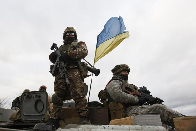 Ukrainian servicemen ride on an armored personnel carrier (APC) at a checkpoint near the eastern Ukrainian town of Debaltseve in Donetsk region, December 24, 2014. (Photo by Valentyn Ogirenko/Reuters)