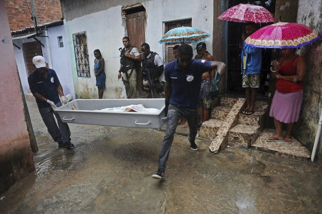 The body of a person identified by the police as a transvestite named Rodrigo, is removed by police forensic workers from the street where he was shot in the Alto do Cabrito slum of Salvador, Bahia State, March 30, 2013. (Photo by Lunae Parracho/Reuters)