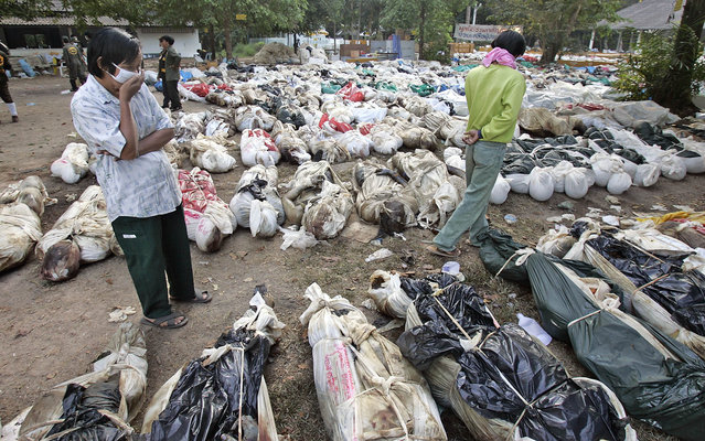 In this December 30, 2004 file photo, Thais walk outside a Buddhist temple, near Takuapa, Thailand, where more than 1,000 bodies have been gathered. (Photo by David Longstreath/AP Photo)