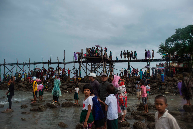 People watch Myanmar military members carrying dead bodies at Sanhlan village on June 8, 2017. Hundreds of people gathered solemnly on a beach in southern Myanmar awaiting news of their loved ones as rescuers worked to pull bodies from the Andaman Sea after a military plane crashed with more than 120 people on board. (Photo by Ye Aung Thu/AFP Photo)