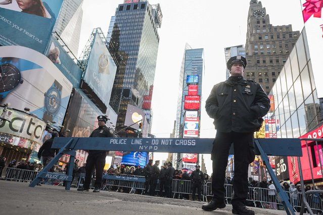 New York City police officers stand guard in Times Square during New Year's Eve celebrations in New York December 31, 2014. (Photo by Keith Bedford/Reuters)