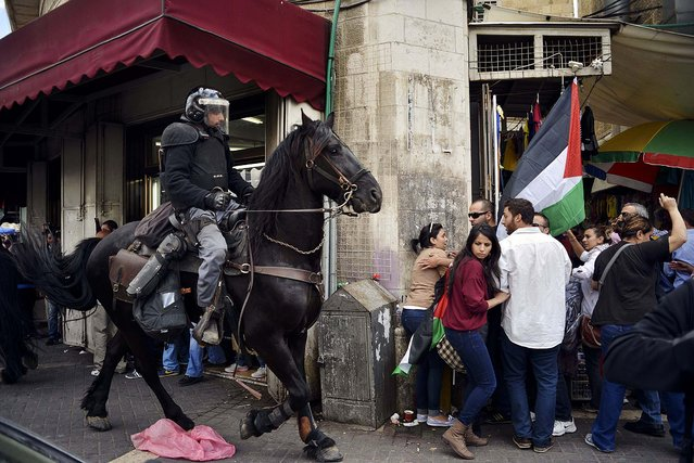 "People move away from an Israeli policeman on a horse as Palestinians mark Nakba Day in Jerusalem, on May 15, 2013. Palestinians annually mark the ""nakba"", or ""catastrophe"" – the term they use to describe their defeat and displacement in the war that followed Israel's founding in 1948. (Photo by Mahmoud Illean/Associated Press)"
