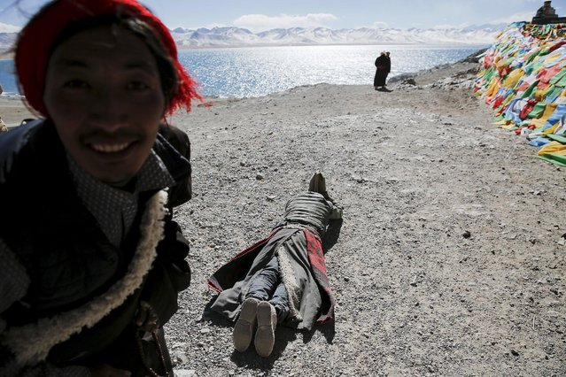 A Tibetan looks at the camera as other one prostrates himself above Namtso lake in the Tibet Autonomous Region, China November 17, 2015. (Photo by Damir Sagolj/Reuters)