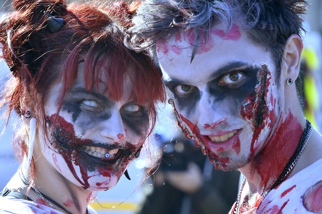 "People wearing costumes pose for a photograph as they participate in the annual ""Zombie Walk"" in Bordeaux, France on October 22, 2016 .Several hundred people wearing costumes and makeup took part in the walk which was authorized despite the state of emergency. (Photo by Georges Gobet/AFP Photo)"