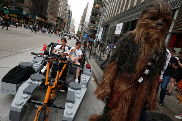 Two girls sit in a Lego Millennium Falcon-themed pedicab as a person dressed as Chewbacca stands by on 6th Avenue in Manhattan in New York City, New York, U.S., May 4, 2018. (Photo by Mike Segar/Reuters)