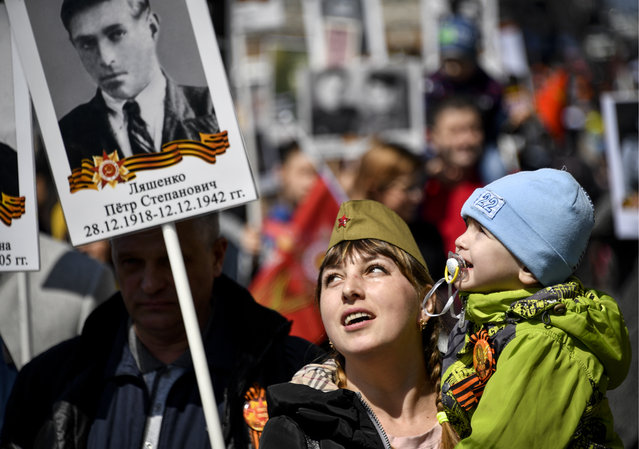 People hold portraits of their relatives who fought in World War II during an Immortal Regiment march on the day of the 73 rdanniversary of the victory over Nazi Germany in the Great Patriotic War of 1941-1945, the Eastern Front of the Second World War in Vladivostok, Russia on May 9, 2018. (Photo by Yuri Smityuk/TASS)