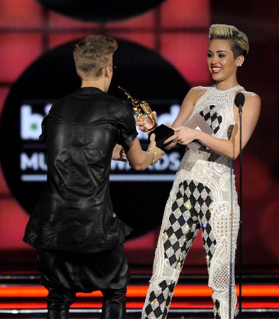 Miley Cyrus presents the award for top male artist to Justin Bieber. (Photo by Chris Pizzello/Invision)