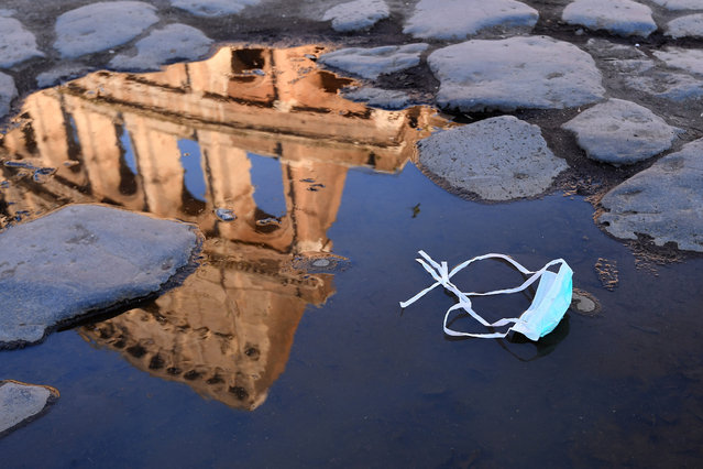 The Colosseum, that will be closed following the government's new prevention measures on public gatherings, is reflected in a puddle where a face mask was left, in Rome, Sunday, March 8, 2020. Italy announced a sweeping quarantine early Sunday for its northern regions, igniting travel chaos as it restricted the movements of a quarter of its population in a bid to halt the new coronavirus' relentless march across Europe. (Photo by Alfredo Falcone/LaPresse via AP Photo)