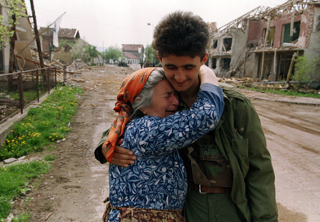 A Muslim woman weeps on the shoulder of a Bosnian soldier in the destroyed downtown area of Vitez, Bosnia, Sunday, May 2, 1993. Vitez, where British U.N. soldiers are based, has been the site of intense fighting in recent weeks. Bosnian Serb leader Radovan Karadzic, threatened with Western military intervention and pressure from his patrons in Yugoslavia, approved a plan Sunday to end a year of ethnic warfare. (Photo by David Brauchli/AP Photo)