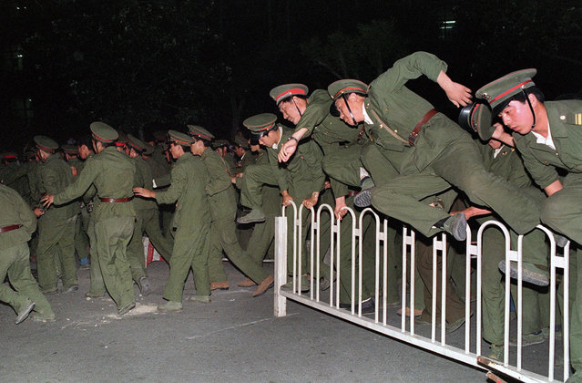 People's Liberation Army (PLA) soldiers leap over a barrier on Tiananmen Square on June 4, 1989, during heavy clashes with people and dissident students. The PLA was reportedly under orders to clear the square by 6:00 am, with no exceptions. (Photo by Catherine Henriette/AFP Photo)