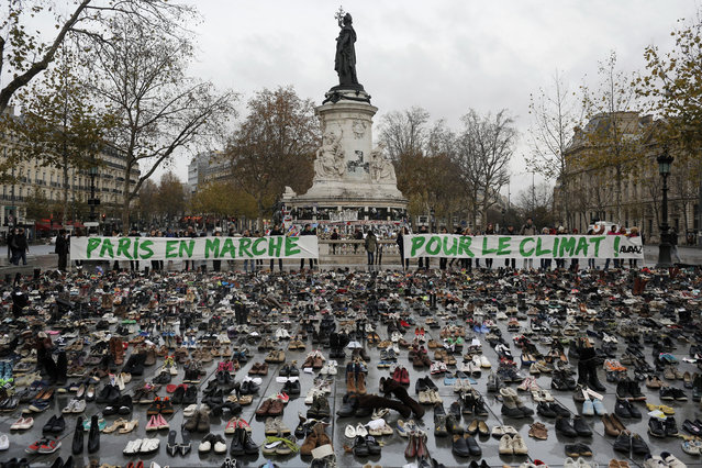 """Hundreds of pairs of shoes are displayed at the place de la Republique, in Paris, as part of a symbolic and peaceful rally called by the NGO Avaaz """"Paris sets off for climate"""", Sunday, November 29, 2015. (Photo by Laurent Cipriani/AP Photo)"""