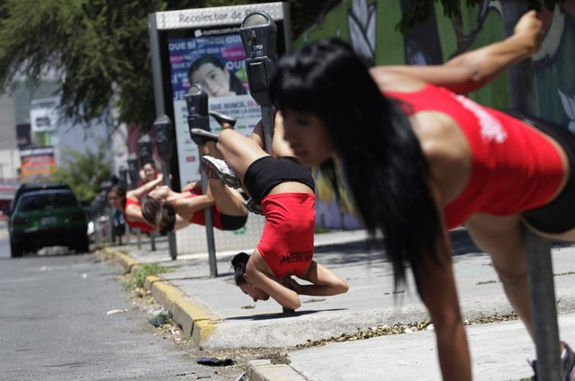 "Women perform a pole dancing routine during the national day celebration of ""Urban Pole"" dance along a street in Monterrey, Mexico, on June 9, 2013. (Photo by Daniel Becerril/Reuters)"