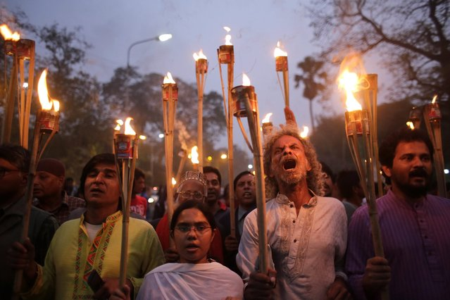 Members of the Ganajagaran Mancha shout slogans as they attend a torch light procession protesting the comments from Pakistan after the execution of Jamaat-e-Islami leader Ali Ahsan Mohammad Mujahid and Salauddin Quader Chowdhury for war crimes in Dhaka, Bangladesh, 02 December 2015. (Photo by Abir Abdullah/EPA)