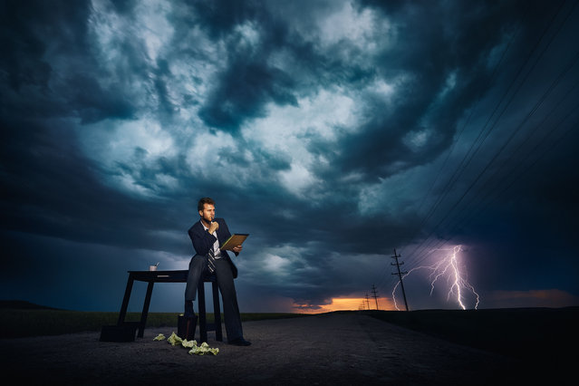 A thrill-seeking snapper has shot a powerful series of images featuring people carrying out everyday chores in front of giant storms. Benjamin Von Wong's surreal scenes include individuals ironing, barbecuing, playing video games and even sitting on the toilet – seemingly unaware of the threatening situations approaching. Here: Models pose in front of a storm in Cheyenne Wyoming. (Photo by Benjamin Von Wongs/Caters News)