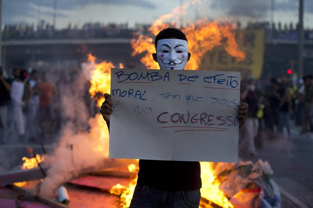 """A protester holds a sign that reads in Portugues """"throw tear gas to the congress"""" during a demonstration in Belo Horizonte, Brazil, Wednesday, June 26, 2013. Brazilian anti-government protesters in part angered by the billions spent in World Cup preparations and police clashed Wednesday near the stadium hosting a Confederations Cup football match, with tens of thousands of demonstrators trying to march on the site confronting police firing tear gas and rubber bullets. (Photo by Victor R. Caivano/AP Photo)"""