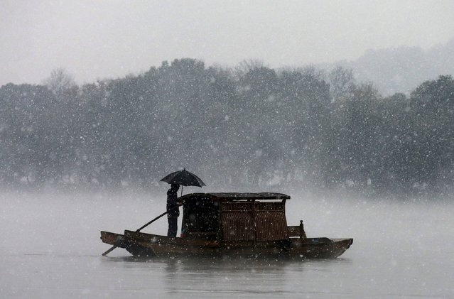 A man holds an umbrella to shield against snowfall as he rows a boat on the West Lake in Hangzhou, Zhejiang province, China, December 5, 2015. (Photo by Reuters/Stringer)