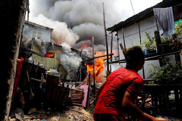 A resident throws water at his house on fire at a residential neighbourhood of an informal settlement, in Muntinlupa, Metro Manila, Philippines on June 21, 2018. (Photo by Erik De Castro/Reuters)