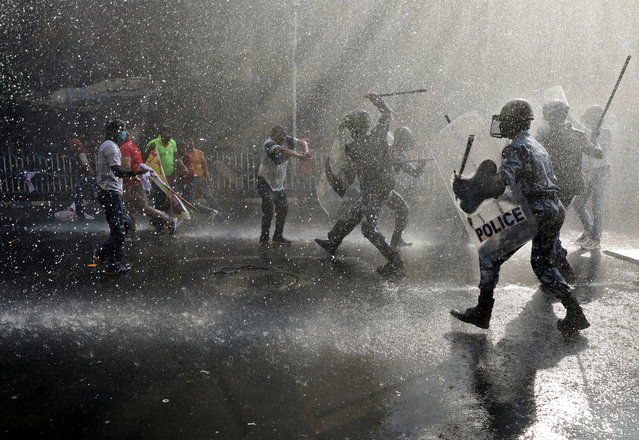 Police officers wield their batons against activists from various student unions amidst droplets by a police water cannon, during a protest march demanding jobs and better education facilities, in Kolkata, India, February 11, 2021. (Photo by Rupak De Chowdhuri/Reuters)