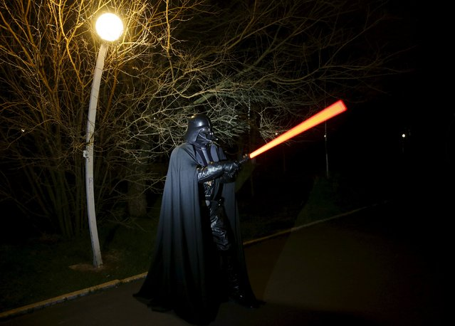 Darth Mykolaiovych Vader, who is dressed as the Star Wars character Darth Vader, poses for a picture as he demonstrates exercises with a lightsaber in a park in Odessa, Ukraine, December 3, 2015. (Photo by Valentyn Ogirenko/Reuters)