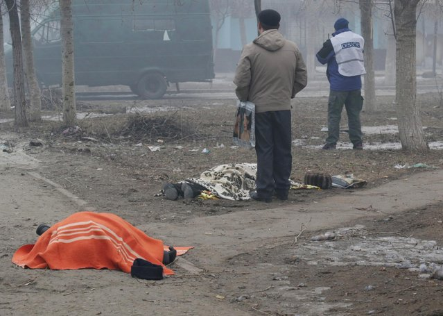 Two dead bodies lay on the ground in a residential area in Mariupol, Ukraine, an OSCE member in the background right, Saturday, January 24, 2015. (Photo by Sergey Vaganov/AP Photo)