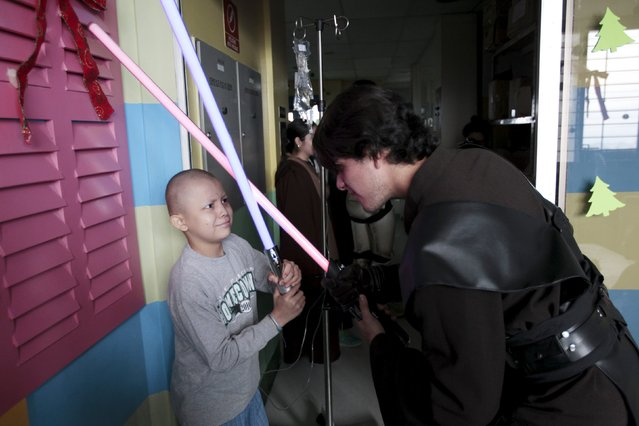 A cosplayer dressed as Anakin Skywalker from the Star Wars movie series interacts with a child during a charity event organised by the El Salvador Star Wars fan club at the Benjamin Bloom National Children's Hospital in San Salvador, El Salvador December 14, 2015. (Photo by Jose Cabezas/Reuters)