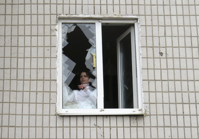 A local resident removes broken glass from a window inside a building near a hospital in Donetsk February 4, 2015. (Photo by Maxim Sergeev/Reuters)