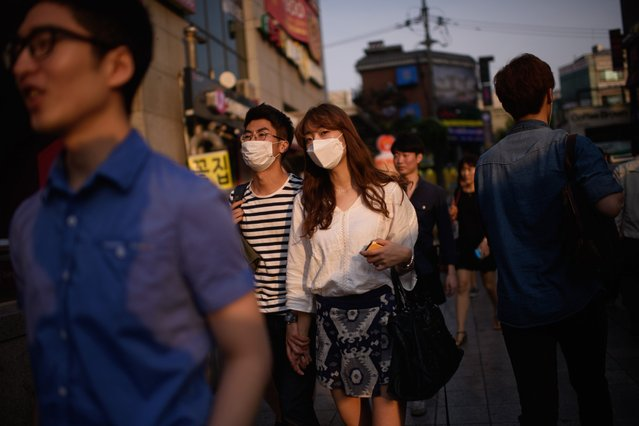 A couple wearing face masks walk on a street in Seoul on June 9, 2015. South Korea on June 9 reported its seventh death from Middle East Respiratory Syndrome (MERS) as the government – concerned about the economic impact – said it hoped to end the crisis this week. (Photo by Ed Jones/AFP Photo)