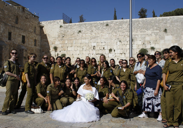 A bride poses for a photograph with Israeli soldiers at the Western Wall, Judaism's holiest prayer site, during a visit to Jerusalem's Old City June 23, 2009. (Photo by Darren Whiteside/Reuters)