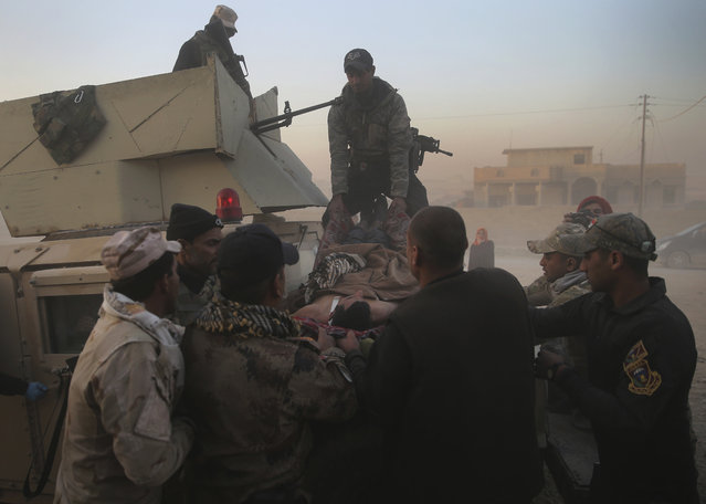 Iraqi special forces soldiers from the medical unit, carry an injured man who was wounded by a mortar shell during the fighting between the Islamic State militants and the Iraqi forces, at a field hospital, in the Samah front line neighborhood, in Mosul, Iraq, Sunday, November 27, 2016. (Photo by Hussein Malla/AP Photo)