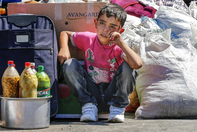 A Syrian boy sits beside his family's belongings as they wait for a vehicle to pick them up after entering the Turkish border gate, on September 6, 2013. The U.N. refugee agency UNHCR said that a near tenfold increase over the past 12 months in the rate of refugees crossing Syria's borders into Turkey, Iraq, Jordan and Lebanon – to a daily average of nearly 5,000 men, women and children – had pushed the total living abroad above two million. (Photo by Umit Bektas/Reuters)