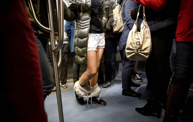 """A girl rides on a train as she takes part in the No Pants Subway Ride in Bucharest, Romania, Sunday, January 10, 2016. The No Pants Subway Ride began as a stunt in 2002 in New York and has taken place in cities around the world since then. Organizers call it """"an international celebration of silliness"""" and are organizing it in dozens of cities on Sunday. (Photo by Andreea Alexandru/Mediafax via AP Photo)"""