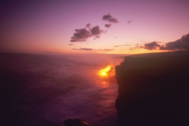 Lava from the Kilauea volcano flows into the sea at sunset, in Kilauea, Hawaii. (Photo by Kirk Aeder/Barcroft Media)
