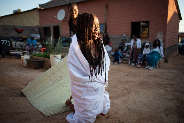 """""""Sangoma"""" initiate Dipuo Banda (C) is led out of her teachers shack while she remains in a trance like state prior to dancing during her 3 day initiation ceremony with her teacher, family, friends and students in the Alexandra Township in Johannesburg, South Africa, 14 May 2021. Sangomas, the Zulu term for Medicine Women or traditional healers, fulfill different social and political roles in the community, including divination, physical healing, emotional and spiritual illnesses, directing birth or death rituals and finding lost cattle. (Photo by Kim Ludbrook/EPA/EFE)"""