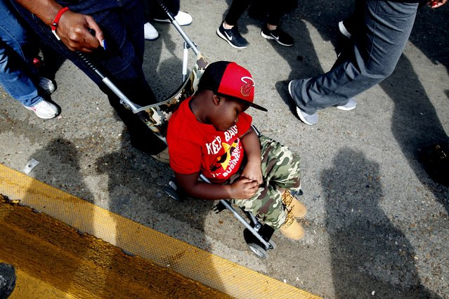 A young boy sleeps as he is wheeled over the Edmund Pettus Bridge during the 50th anniversary of the Selma to Montgomery civil rights march in Selma, Alabama March 8, 2015. REUTERS/Tami Chappell  (UNITED STATES - Tags: POLITICS ANNIVERSARY SOCIETY)