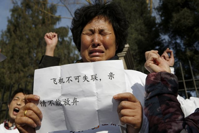 "Liu Guiqiu, whose son was onboard the missing Malaysia Airlines flight MH370, cries while other family members shout slogans during a gathering of family members of the missing passengers outside the Malaysian embassy in Beijing March 8, 2015. Malaysian and Chinese officials say they are committed to the search for MH370 and in assisting families who are still waiting for concrete information on what happened to their loved ones a year ago. The sign reads, ""A plane cannot lose contact; and families cannot give up their affection for their relatives."" 