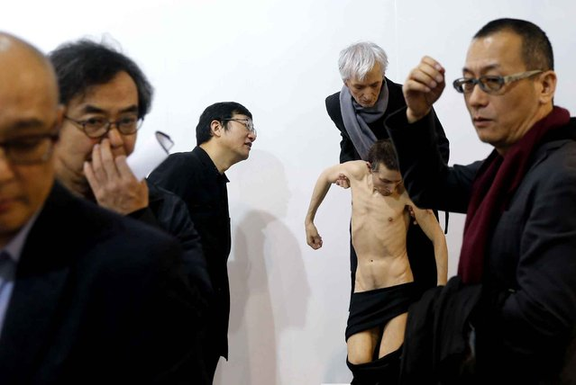 "Visitors gesture besides an artwork ""Untitled (Standing Pieta)"" created by Australian artist Sam Jinks during the VIP preview of the art fair Art Basel in Hong Kong Friday, March 13, 2015. (Photo by Kin Cheung/AP Photo)"