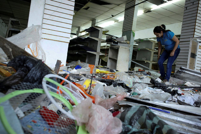 A worker looks for valuables among the damaged goods in a store after it was looted, in La Fria, Venezuela, December 19, 2016. (Photo by Carlos Eduardo Ramirez/Reuters)
