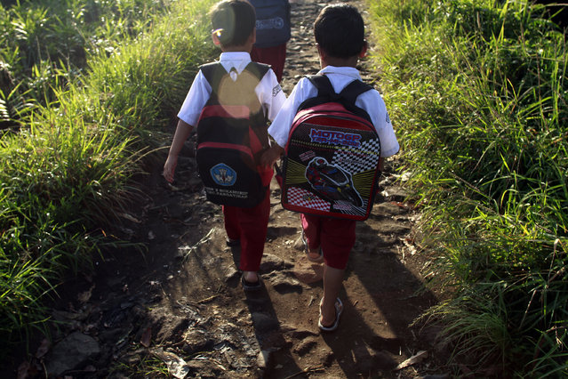 Dihan, right, walks with his friends as they go to elementary school. (Photo by Rezza Estily/JG Photo)