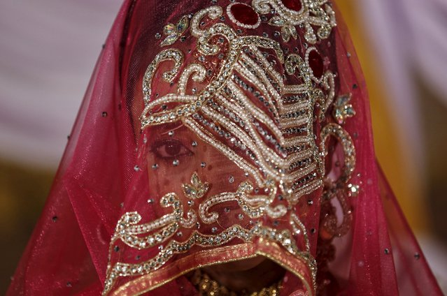 A Muslim bride waits for the start of a mass marriage ceremony in Mumbai, India, January 27, 2016. A total of 12 Muslim couples took their wedding vows during the mass marriage ceremony organised by a Muslim voluntary organisation, organisers said. (Photo by Danish Siddiqui/Reuters)