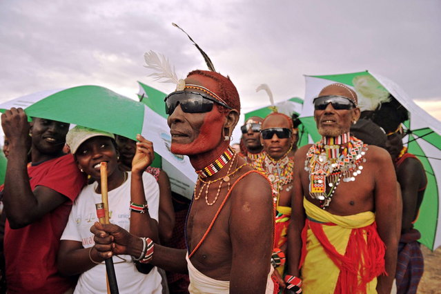 "Members of the Rendile tribe are pictured before total hybrid eclipse in Sibiloi national Park in Turkana on November 3, 2013. Astronomy enthusiasts in Kenya caught a partial glimpse of a rare ""Hybrid Total Eclipse"" which hasn't been witnessed in Africa for over 40 years, though weather hampered a view of the complete eclipse. (Photo by Carl de Souza/AFP Photo)"