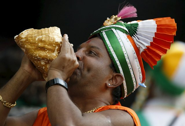 A fan of India's cricket team blows into a sea shell during their Cricket World Cup quarter final match against Bangladesh in Melbourne, March 19, 2015. (Photo by Brandon Malone/Reuters)