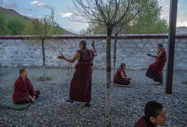 Tibetan Buddhist monks debate in the courtyard during a government organized visit to the Buddhist College of the Tibet Autonomous Region on May 31, 2021 in Qushui County, outside Lhasa, Tibet Autonomous Region, China. (Photo by Kevin Frayer/Getty Images)
