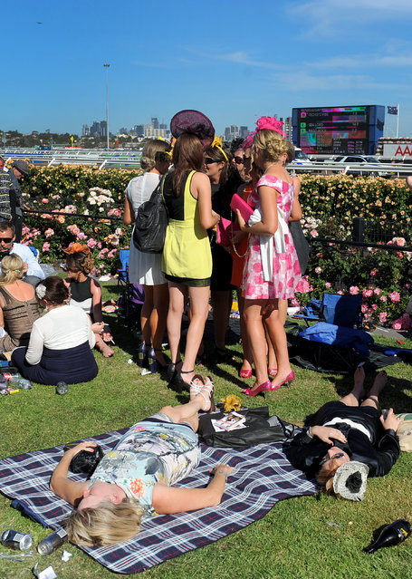 Race goers enjoy the atmosphere at the end of the day at the Melbourne Cup at Flemington Racecourse in Melbourne, Tuesday, November 5, 2013. (Photo by Joe Castro/AAP/Press Association Images)